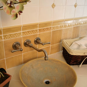 Antigua Colonial Relief Tiles in Sand with Matte White Field Tiles Create a Relaxing Spa Bath