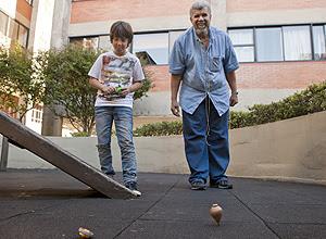 O aposentado Samuel Mello Silva, 61, com o pião de madeira, disputa com Leonardo Azevedo, 9, com o Beyblade