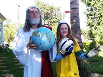 Inri Cristo segura um globo terrestre enquanto uma discípula, com luvas de goleiro, ergue uma bola de futebol (Foto: Alysluz Varella/Soust)