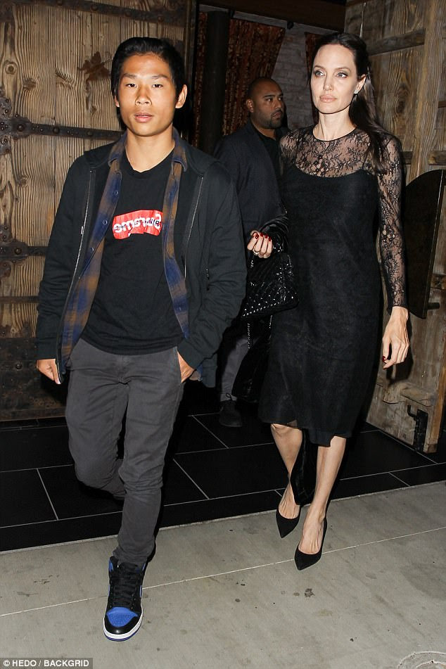 Simply chic:Angelina looked elegant in an LBD with lace sleeves as she stepped out beside her casually dressed son, Pax