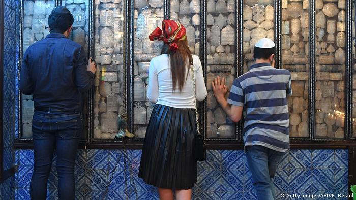 Jewish pilgrims face a wall in prayer