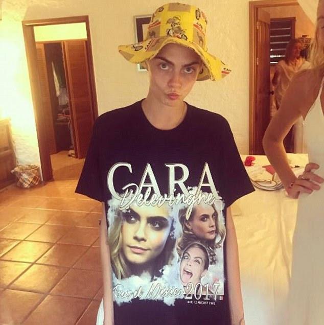 Modelo do momento: Cara brilhou uma calda quando ela posava em uma camiseta com o rosto e um chapéu de balde estranho