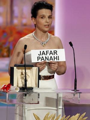 A atriz Juliette Binoche segura uma placa com o nome do  diretor iraniano Jafar Panahi