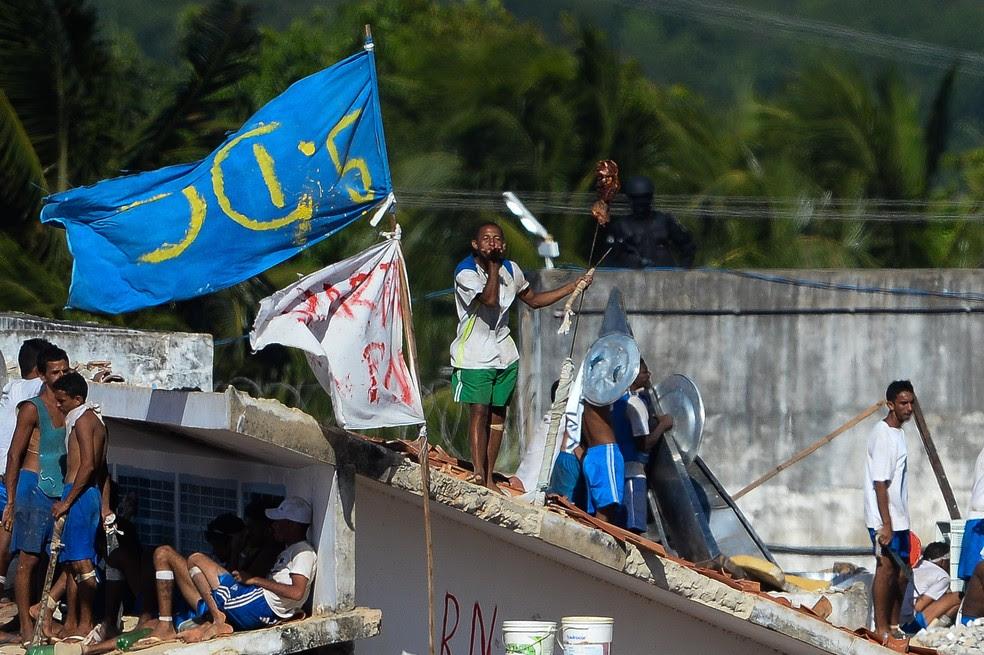 Presos são vistos no telhado durante uma rebelião na penitenciária de Alcaçuz (Foto: Andressa Anholete/AFP)