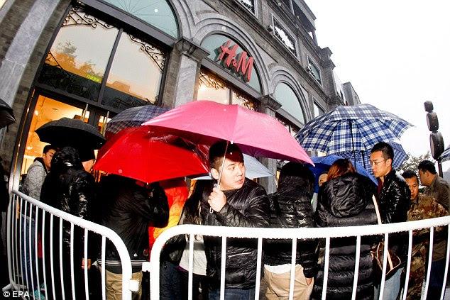 Compradores fila na chuva antes do lançamento da Versace para a H & M coleção de fora de uma loja H & M em Pequim