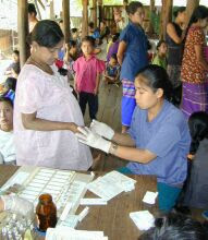 Pregnant woman having a fingerprick performed by a health worker for diagnosis of malaria in a semi-open clinic
