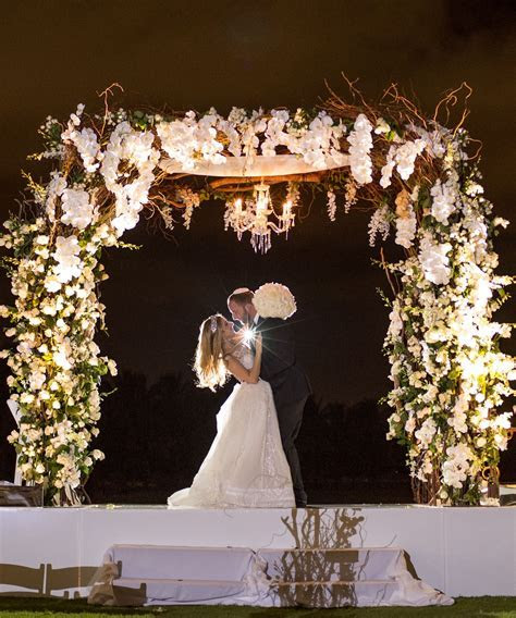 Outdoor evening wedding ceremony. White chuppah with