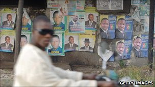 A man races past election campaign posters on his motorbike in Nigeria