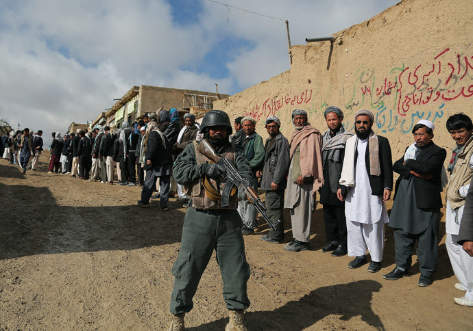An Afghan policeman keeps watch as Afghan voters line up to vote at a local polling station in Ghazni on April 5, 2014. (AFP Photo / Rahmatullah Alizadah)