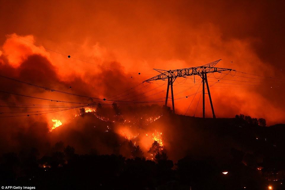 Os incêndios ardiam através encostas em Les Pennes-Mirabeau, perto de Marselha, na noite passada, mesmo colocando em risco linhas de energia