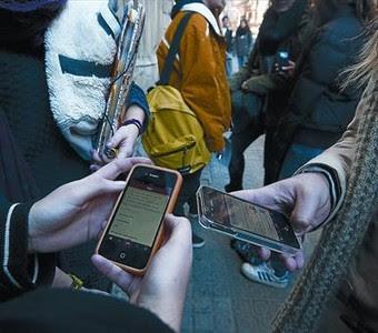Unos jóvenes consultan sus teléfonos móviles en un instituto de Barcelona.