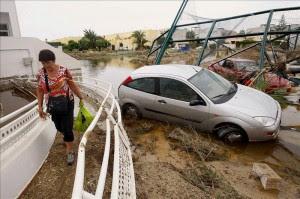 Una mujer pasa junto a varios vehículos arrastrados por las lluvias torrenciales caídas en las últimas horas en la localidad almeriense de Vera.EFE