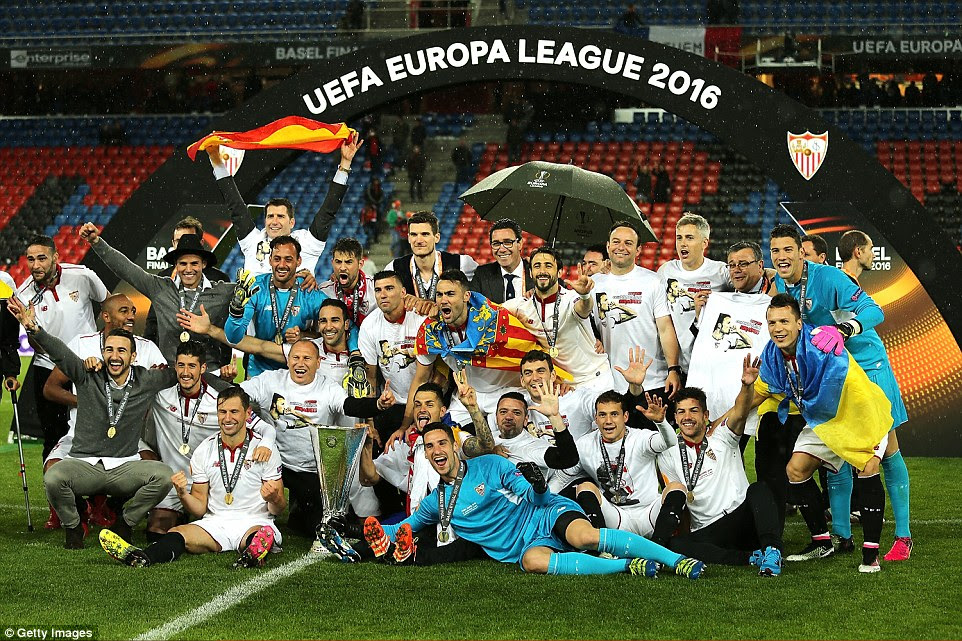 Sevilla players pose with the trophy after completing a stunning second-half comeback to win a record third consecutive Europa League