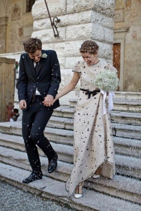einen elfenbeinfarbenen polka-Punkt-Hochzeits-Kleid mit kurzen ärmeln und eine schwarze Schärpe, dazu passende Schuhe