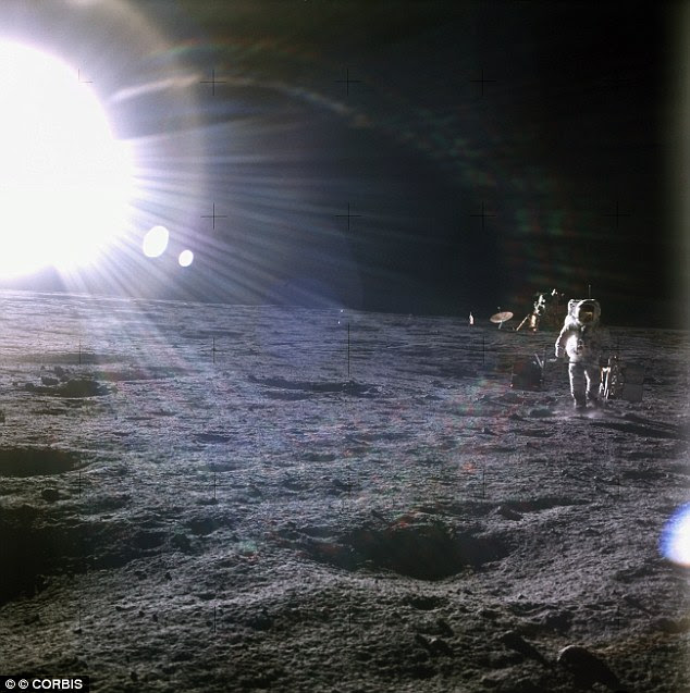 A brilliant sun shines above the Apollo 12 base on the Moon's surface as one of the astronauts walks away from the lunar module Intrepid