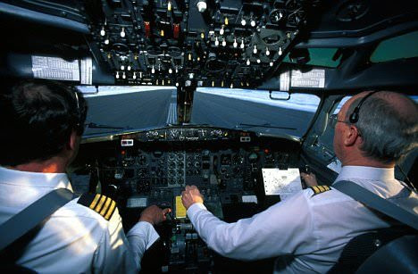 Pilots in the cockpit of an aircraft.
