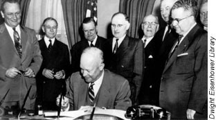 Photo of Officials watching President Einsenhower sign the Federal-Aid Highway Act of 1954. There is no photo for the 1956 Act.