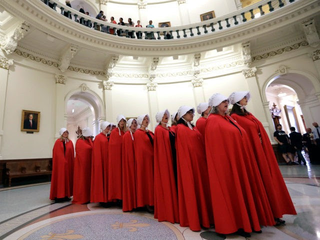 """Activists dressed as characters from """"The Handmaid's Tale"""" chant in the Texas Capitol Rotunda as they protest SB8, a bill that would require health care facilities, including hospitals and abortion clinics, such as Planned Parenthood, to bury or cremate any fetal remains whether from abortion, miscarriage or stillbirth, and they would be banned from donating aborted fetal tissue to medical researchers, Tuesday, May 23, 2017, in Austin. (AP Photo/Eric Gay)"""