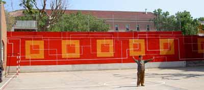 El artista Manuel Ros, detras: el mural del Brusi, en proceso