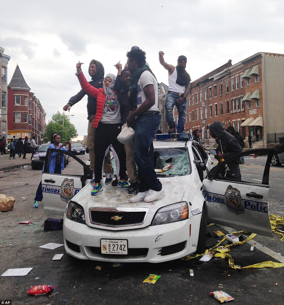 People stand on top of a  police car as night falls in Baltimore