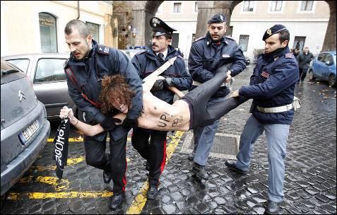 Una activista del grupo Femen, es llevada en volandas tras un acto de protesta en la plaza de San Pedro en el  Vaticano.