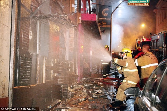 Firefighters battle to put out the fire which tore through the Kiss Club in Santa Maria, southern Brazil