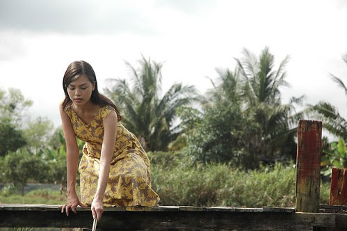 Miss Carol (Carmen Soo) tries to pick up books from the pond