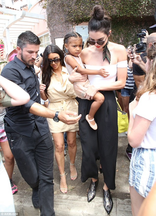 Quite a load: Kim let her younger half-sister and doting auntie Kendall Jenner, 20, do the heavy lifting and carry three-year-old North West to the car