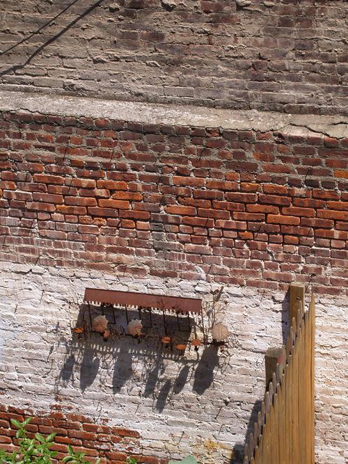 hanging metal scene on a brick wall