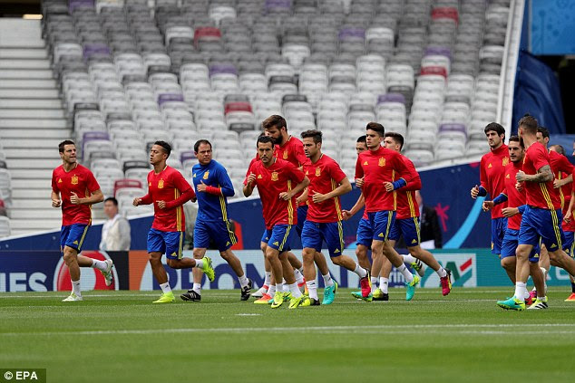 Spain's players jog with a coach as they train inside Stade Municipal de Toulouse in the south of France