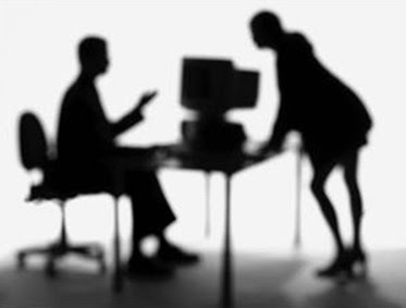 Blurred silhouettes of people and a computer