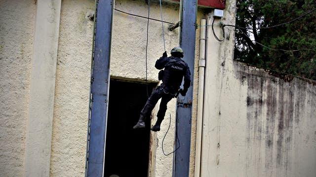 En forma simultánea un grupo ingresa por la puerta y por las ventanas de la vivienda, al tiempo que se arrojan cargas explosivas inertes para aturdir a los ocupantes