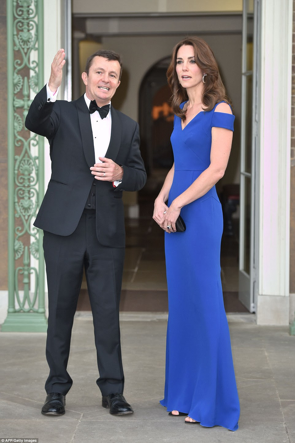 Kate chats to an aide as she prepared to greet guests at the reception in Kensington Palace's gardens