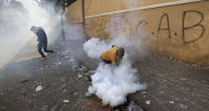 An Egyptian protestor wearing a gas mask reaches to pick up a tear gas canister fired by security forces during clashes near the Interior Ministry in Cairo, Sunday, Feb. 5, 2012. (AP Photo/Muhammed Muheisen)