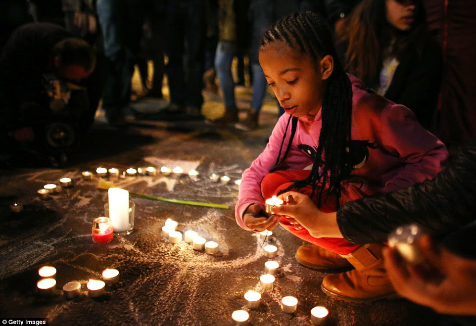 Rest in peace:A young girl lights a candle at the Place de la Bourse following today's attacks  in Brussels, in which 31 people were killed