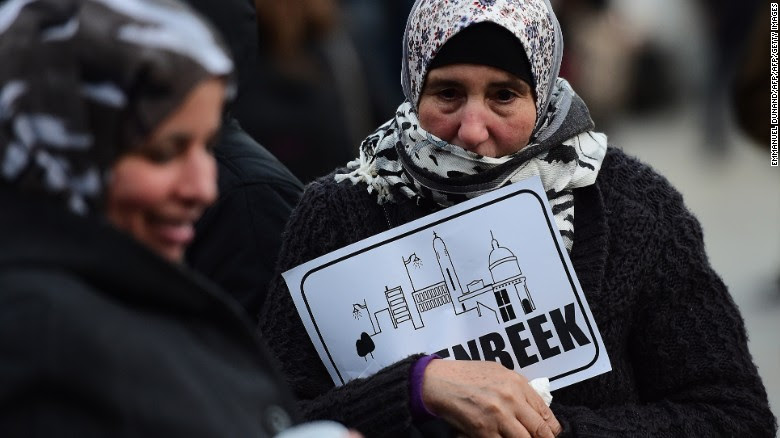 """A woman holds a piece of paper reading """"Molenbeek"""" during a candlelit vigil to the victims of the Paris attacks in Brussels."""