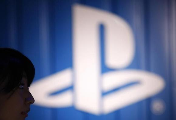 The logo of Sony Corp's PlayStation is seen next to a woman at its booth during the Tokyo Game Show 2014 in Makuhari, east of Tokyo September 18, 2014.  REUTERS/Yuya Shino
