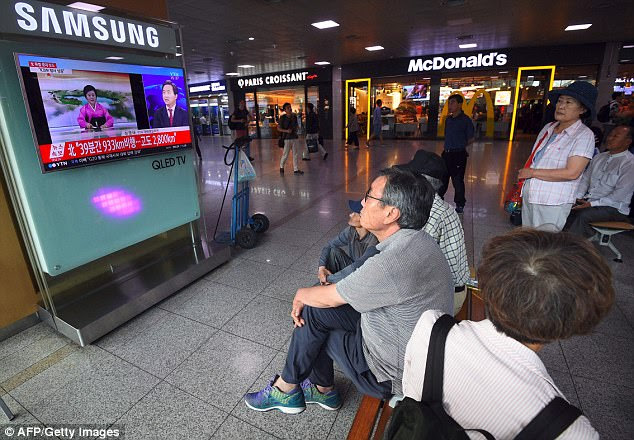 People in Seoul watch a television news broadcast showing a North Korean announcer reading a statement on the country's new ICBM test