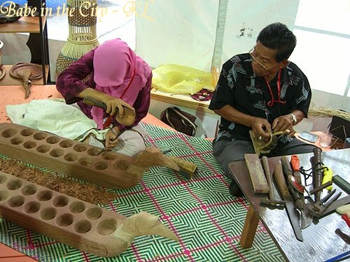 The lady is chiselling away making congkak