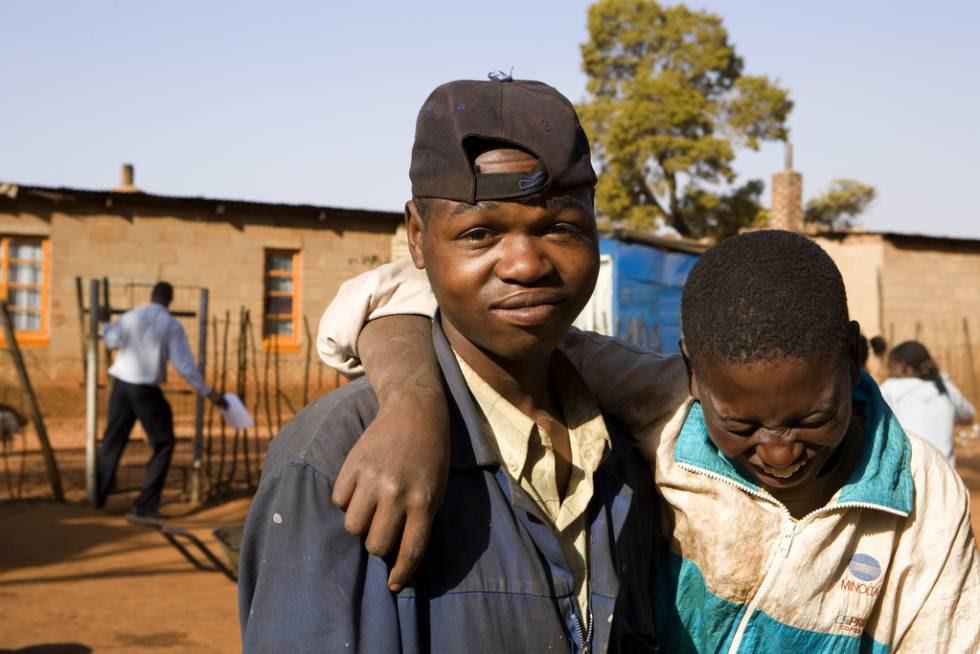 Dos amigos se ríen en el asentamiento temporal en Bapsfontein, a 80 kilómetros de Johannesburgo (Sudáfrica).