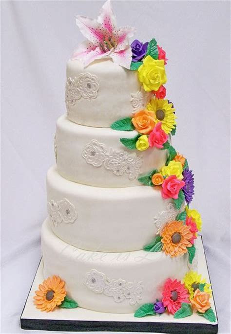 Four tier round white wedding cake with lily on top and
