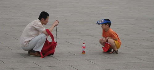 Father and son with flag, camera, and empty drink bottle, Tian'anmen Square