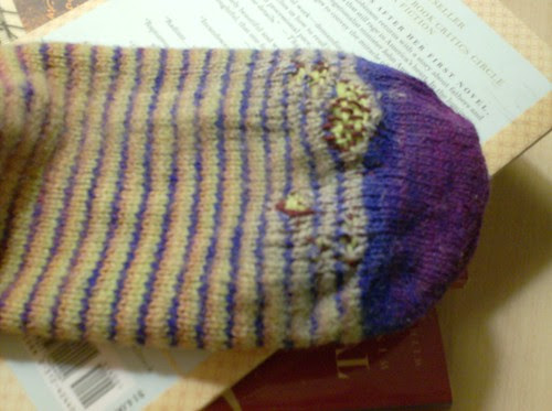 Darned helical stripe handspun socks with a mended hole at the toe