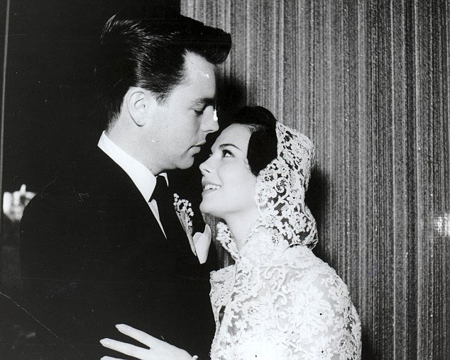 Happy: Actress Natalie Wood pictured with her husband Robert Wagner on their first wedding day in 1957. They divorced only to remarry again six years later