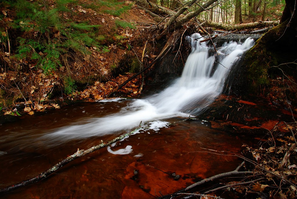 A small seasonal waterfall with a bright red streambed.