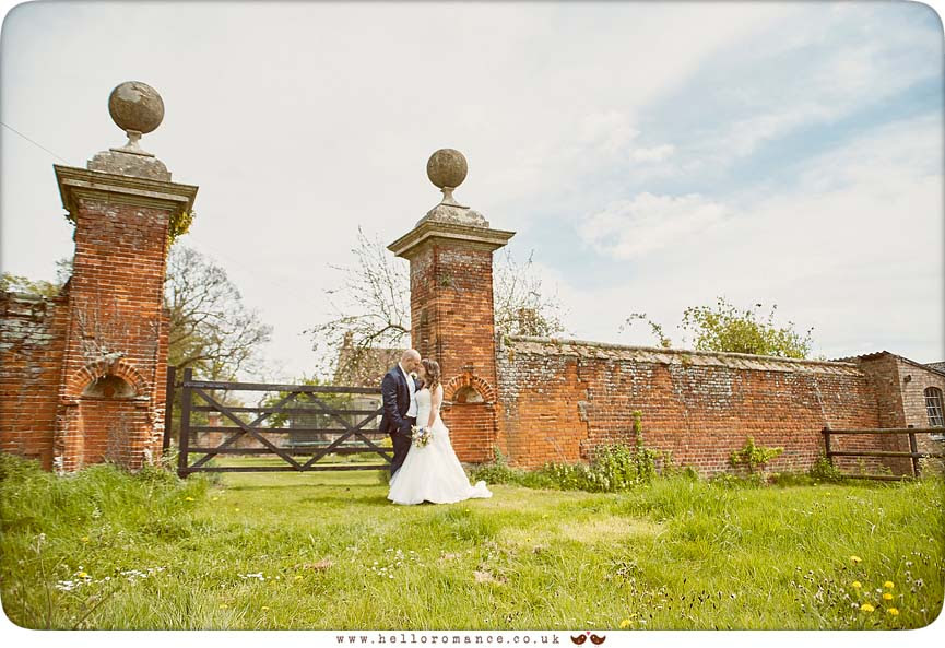 Bride and groom standing by rustic red brick gateway in Hawstead, Suffolk (Suffolk Barn) - www.helloromance.co.uk