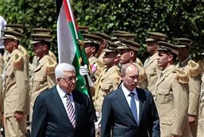 Abbas and Putin walk past an honor guard in Bethlehem Tuesday