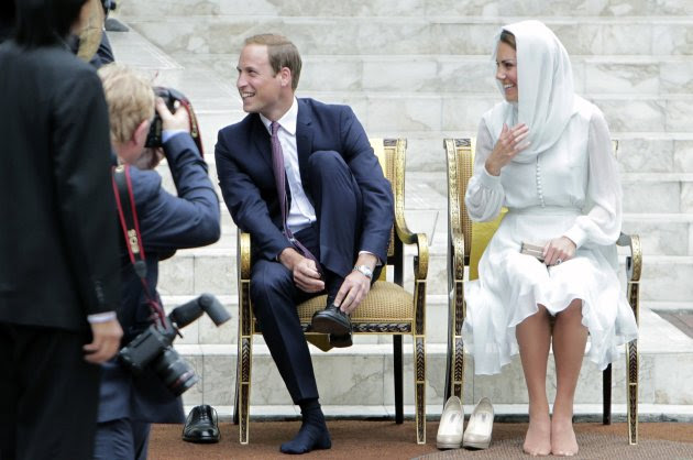 Britain's Prince William and Catherine, Duchess of Cambridge, take off their shoes before visiting the As-Syakirin Mosque at KLCC in Kuala Lumpur