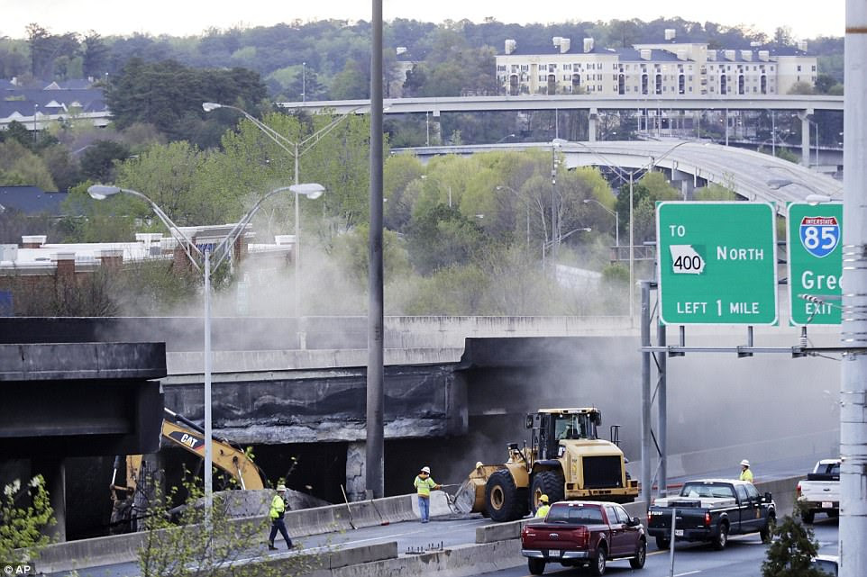 On Friday, crews (pictured) were seen working to restore the bridge after the blaze collapsed a portion of I-85. Atlanta residents will likely face travel chaos as construction crews repair the fragmented section of the exceptionally busy motorway