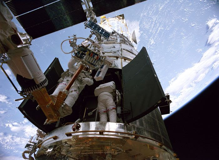 A screenshot of astronauts working on the Hubble Space Telescope during STS-125, in HUBBLE 3D.